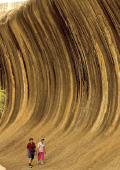 Couple walking at the base of Wave Rock