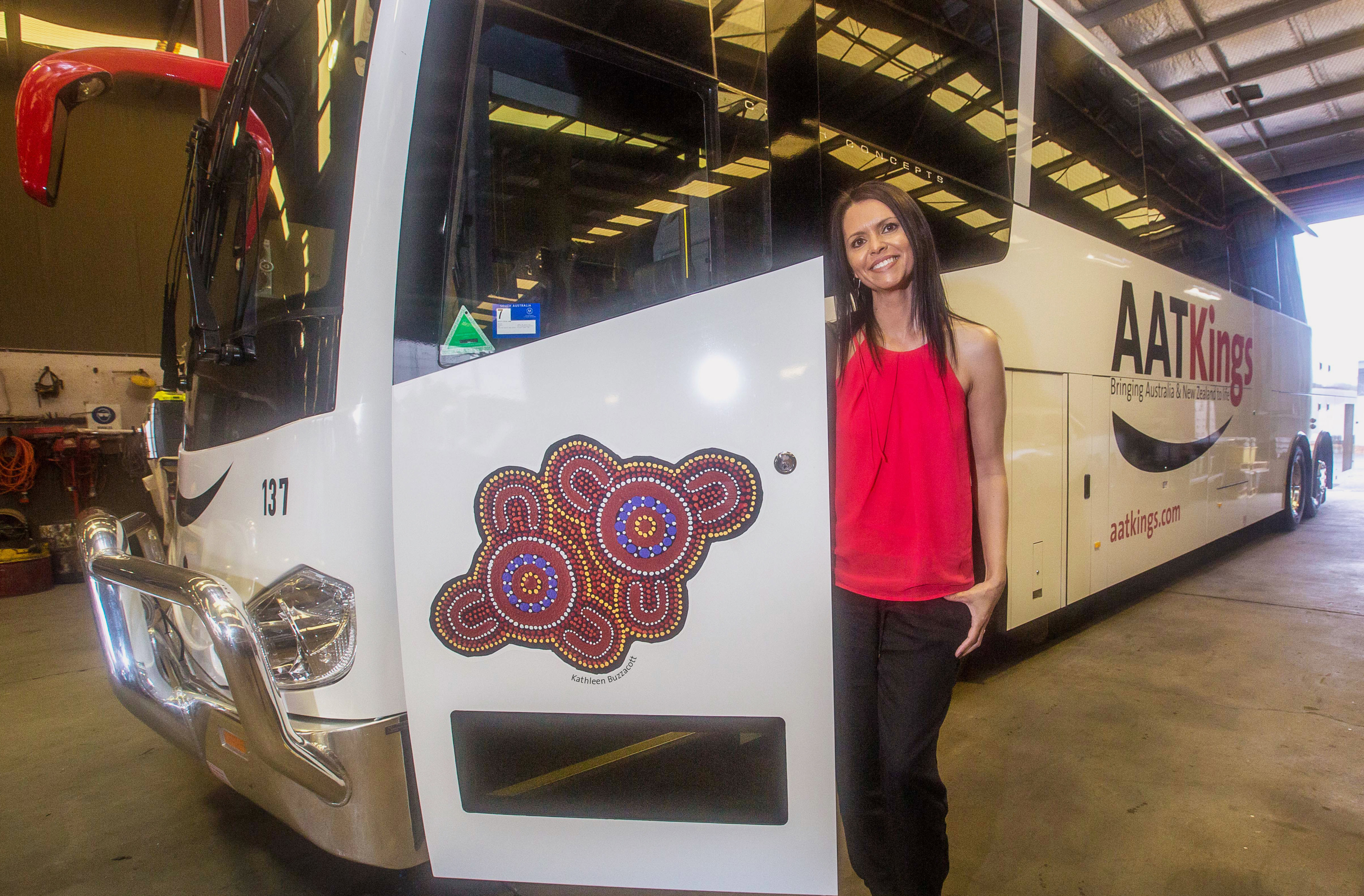 Maruku Artist Kathleen Buzzacott, with her work displayed on an AAT Kings coach in the Red Centre